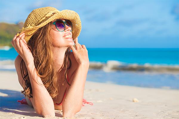 Frau mit Sonnenhut am Strand liegend_shutterstock_572259820_600x400_web