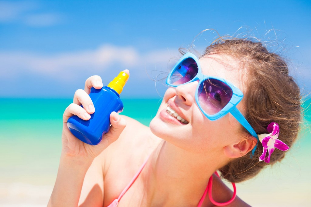 Young,Woman,In,Sunglasses,Holding,Sun,Cream,In,Hand